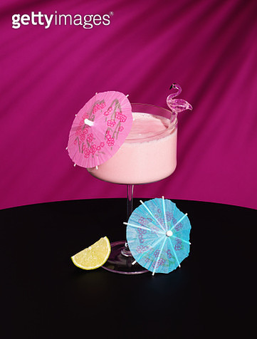 Milky pink cocktail in champagne glass with paper parasols, flamingo stirrer and lime wedge garnish. - gettyimageskorea