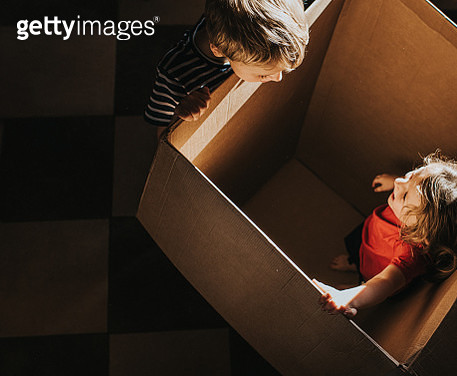 Little Boy standing at the side of a huge box looking in, as a little girl looks back at him from inside the Box - gettyimageskorea