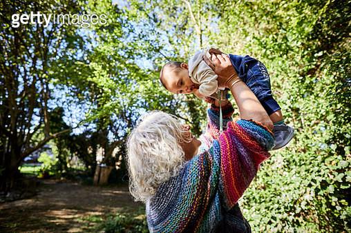 Grandmother holding grandson in garden - gettyimageskorea