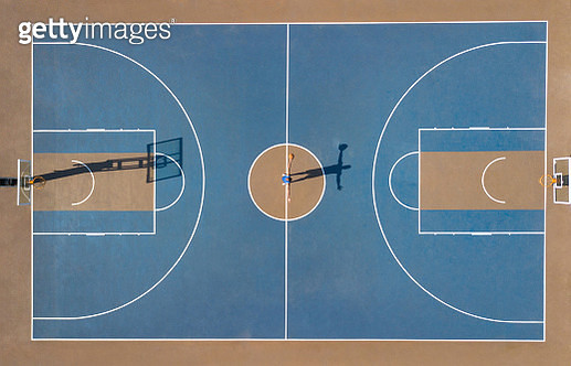 Aerial shot of player and shadow in centre of basketball court - gettyimageskorea