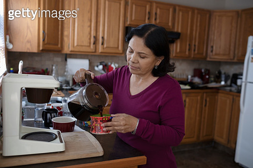 Senior Latinx woman pouring coffee in kitchen - gettyimageskorea