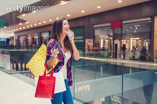 Smiling woman in the shopping mall talking on phone - gettyimageskorea