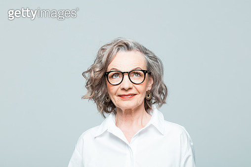 Elderly lady wearing white shirt and glasses standing against grey background, looking up and smiling. Studio shot of female designer. - gettyimageskorea