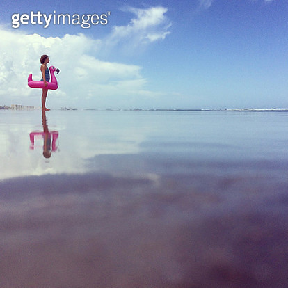 Young girl standing in the surf as she carries an enormous inflatable flamingo inner tube after playing and swimming in the ocean. Travel with kids. Family vacation. Childhood. - gettyimageskorea