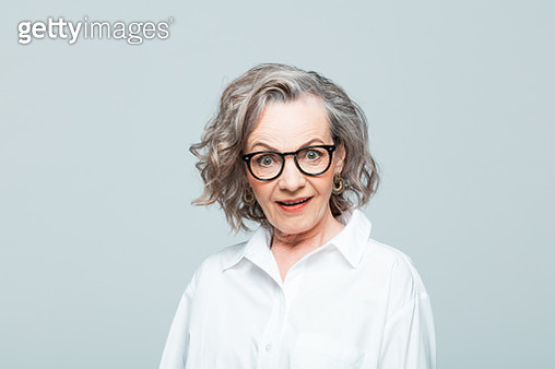 Elderly lady wearing white shirt and glasses standing against grey background, staring at camera with mouth open. Studio shot of female designer. - gettyimageskorea
