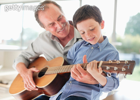 Grandfather teaching grandson to play the guitar - gettyimageskorea
