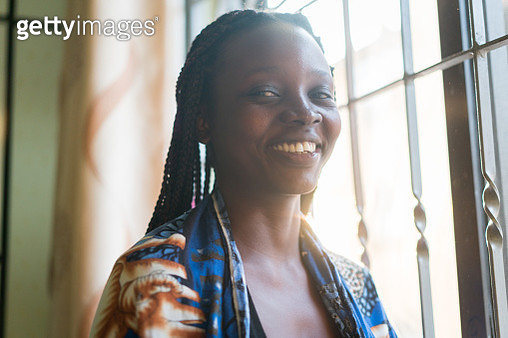 Smiling African American black woman indoors on window - gettyimageskorea