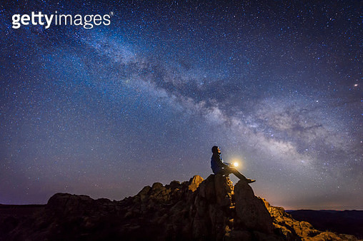 Man sitting under The Milky Way Galaxy with light on his hands. - gettyimageskorea