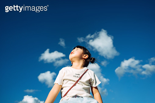 Cute little Asian girl with eyes closed enjoying the warmth of sun and the gentle breeze against beautiful blue sky on a lovely sunny day - gettyimageskorea