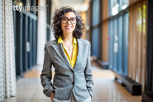 Happy mature businesswoman standing with her hands in pocket outside an auditorium. Smiling female entrepreneur outside convention center. - gettyimageskorea