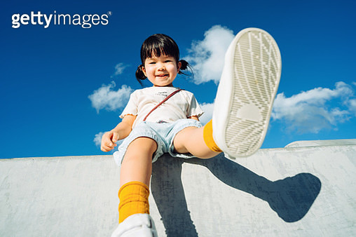Low angle view of cute little Asian girl smiling joyfully and having fun in outdoor park against beautiful blue sky on a lovely sunny day - gettyimageskorea