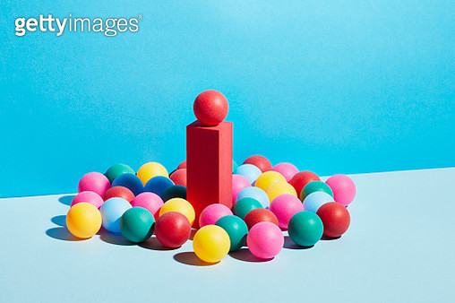 A group of multicoloured spheres around a single red sphere on a pedestal - gettyimageskorea