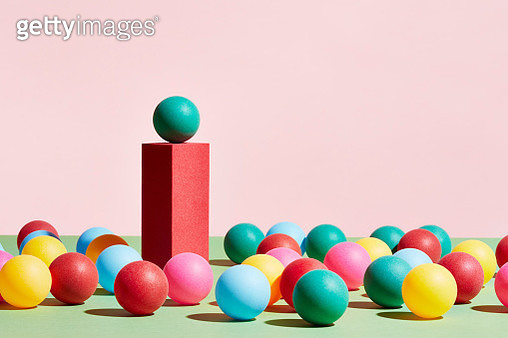 A green sphere stands on top of a pedestal surrounded by a crowd of multicoloured spheres - gettyimageskorea