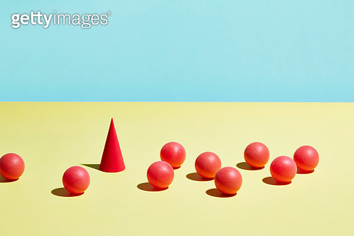 A red cone stands in a group of red spheres - gettyimageskorea