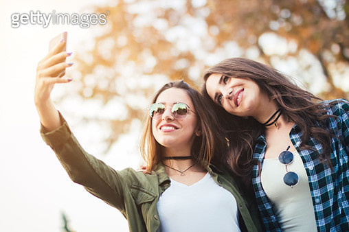 Two beautiful young woman taking selfie in autumn day - gettyimageskorea