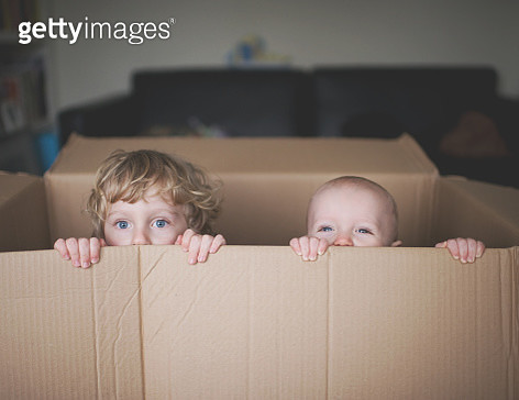 Small kid and baby playing in and looking out of a cardboard box. - gettyimageskorea