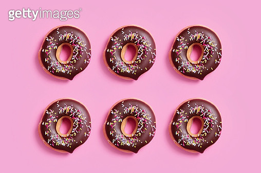 Overhead view of chocolate donuts with sprinkles arranged on pink background - gettyimageskorea