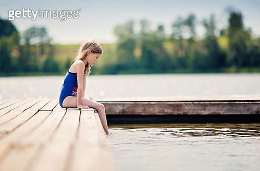 Girl sitting by lake - gettyimageskorea