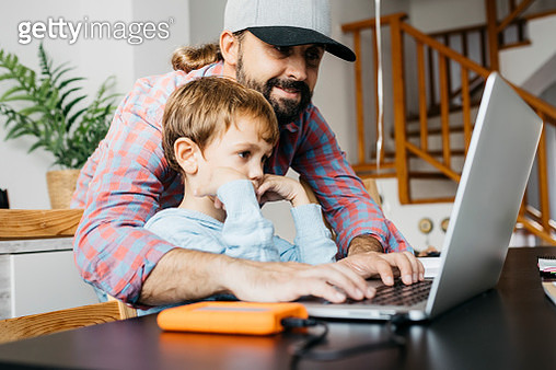 Father and son using laptop together - gettyimageskorea