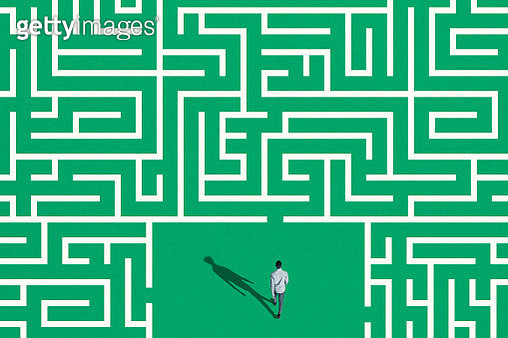 High angle view of young man surrounded by white maze on green background - gettyimageskorea