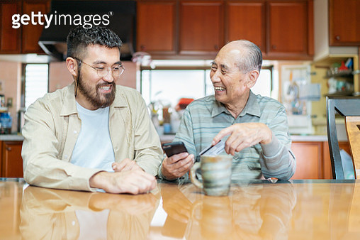 Young man helping his grand father with shopping online - gettyimageskorea