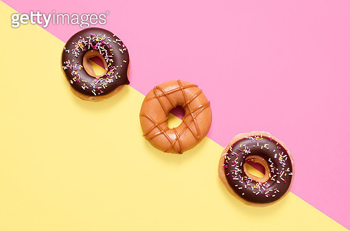 Overhead view of donuts arranged on colored background - gettyimageskorea