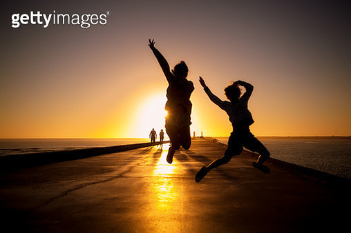 two kids jump into ocean at sunset - gettyimageskorea
