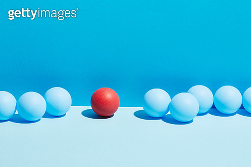 A red sphere stands in a row of blue spheres - gettyimageskorea