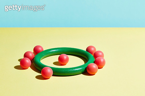 A single red sphere sits inside a green hoop surrounded by red spheres - gettyimageskorea