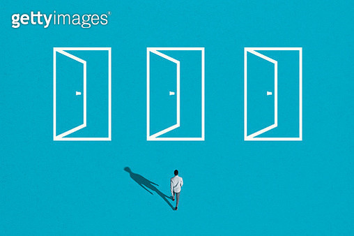 High angle view of young man walking towards white doorways on blue background - gettyimageskorea