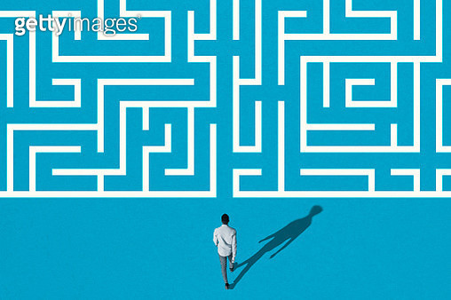 High angle rear view of young man walking towards white maze pattern over blue background - gettyimageskorea