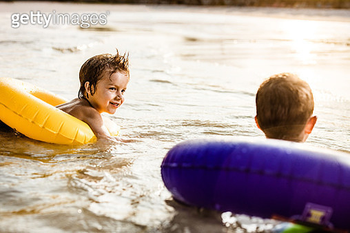 Happy little boy and his friend swimming with inflatable rings in the sea. - gettyimageskorea