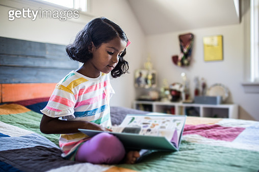 Girl reading book on her bed - gettyimageskorea