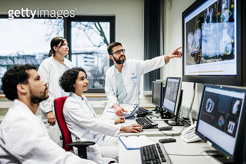 A team of doctors looking at some lab results together on monitors, in an office at the hospital. - gettyimageskorea