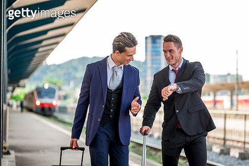 Two businessmen on the train station with suitcases - gettyimageskorea