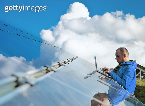 Male engineer with laptop working on solar panels - gettyimageskorea