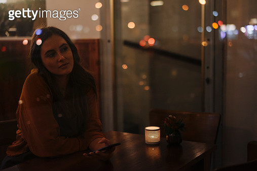 Young woman with cell phone behind windowpane in a restaurant - gettyimageskorea