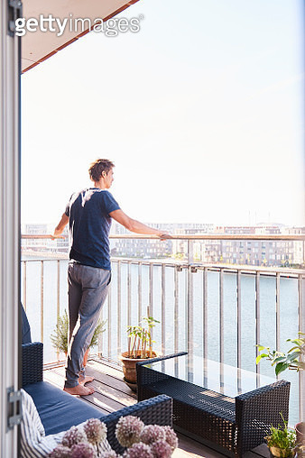 Mid adult man looking out from waterfront apartment balcony - gettyimageskorea