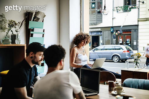 A young woman is sat by the window in a cafe working quietly on her laptop, while two other men work together on a computer. - gettyimageskorea