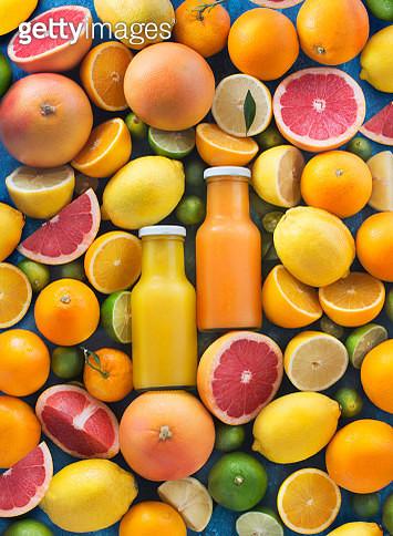 Assorted citrus fruits and juice in bottles. - gettyimageskorea