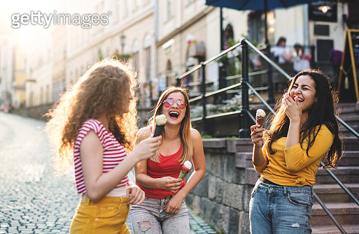 Three cheerful female teenager friends with ice cream standing on the street, laughing. - gettyimageskorea