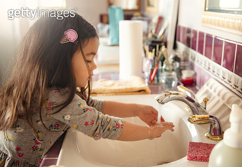 A 3 year old girl washes her hands at the sink after cleaning her paint brushes which can be seen in the background. - gettyimageskorea