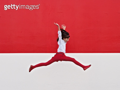 Girl jumping in air at red wall - gettyimageskorea