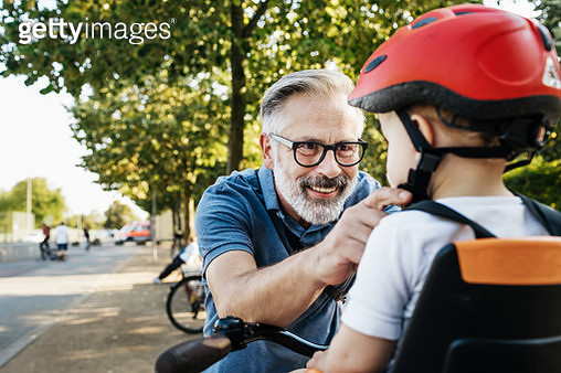 Grandpa Doing Up Grandson's Helmet - gettyimageskorea