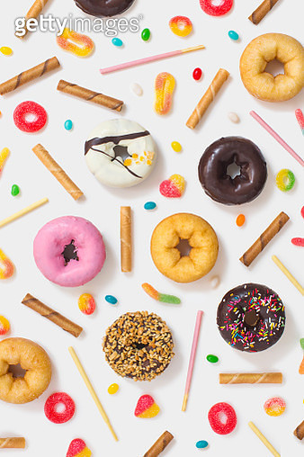 Flat lay various colourful glazed donuts, candy and snacks on white  background. Studio table top shot. - gettyimageskorea