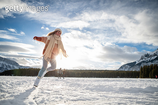 Young woman ice skating on frozen lake at sunset having fun and enjoying winter vacations - gettyimageskorea
