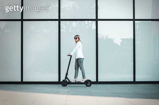 Businesswoman riding a scooter in the city - gettyimageskorea