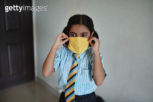 Portrait of a school girl in school uniform wearing face mask as school reopens after a Covid-19 pandemic - gettyimageskorea