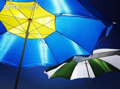 Low Angle View Of Colorful Parasol Against Blue Sky - gettyimageskorea