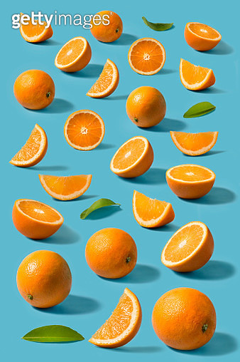 Sliced and whole oranges still life with harsh shadow on bright blue background. Stylised fruit image. - gettyimageskorea